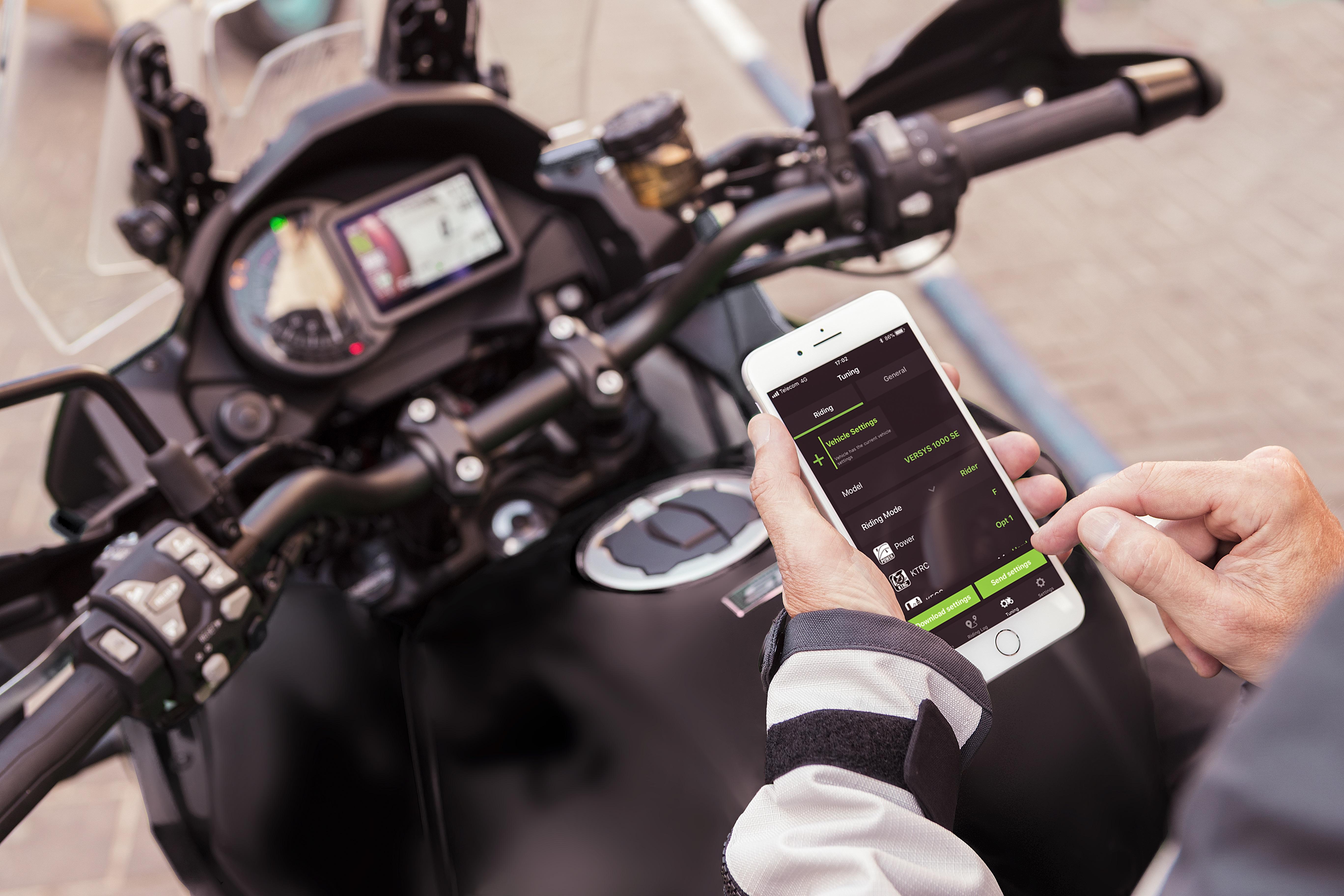 Rider using RIDEOLOGY THE APP on phone on their Kawasaki motorcycle