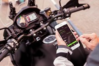 Rider using RIDEOLOGY THE APP on phone on their Kawasaki motorcycle