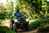 Front three-quarter angle of a person riding an ATV off-road.