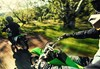 POV angle of person riding a motorcycle on a dirt trail.