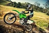 Profile angle of person riding a motorcycle up a dirt hill.