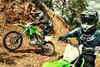 Closeup angle of people riding motorcycles on a dirt trail.