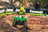 Front angle of person riding an ATV on a dirt track.