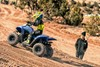 Profile angle of person riding an ATV on a dirt track.