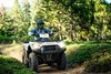 Front angle of person riding an ATV on a dirt trail.